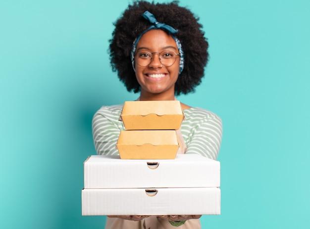 Jonge mooie afro bezorgt vrouw met afhaalmaaltijden pizza en hamburgerdozen