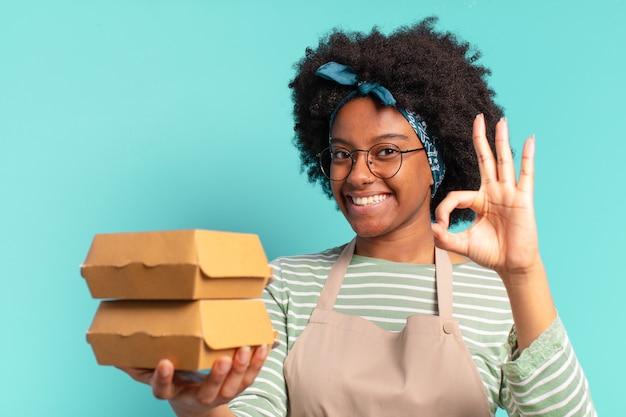 Jonge mooie afro bezorgt vrouw met een meeneem hamburgerdozen