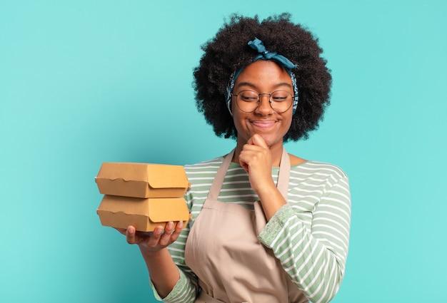 Jonge mooie afro-bezorgvrouw met een afhaalburgerbox