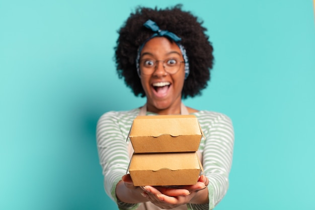 Jonge mooie afro levert vrouw met een meeneem hamburgerdozen