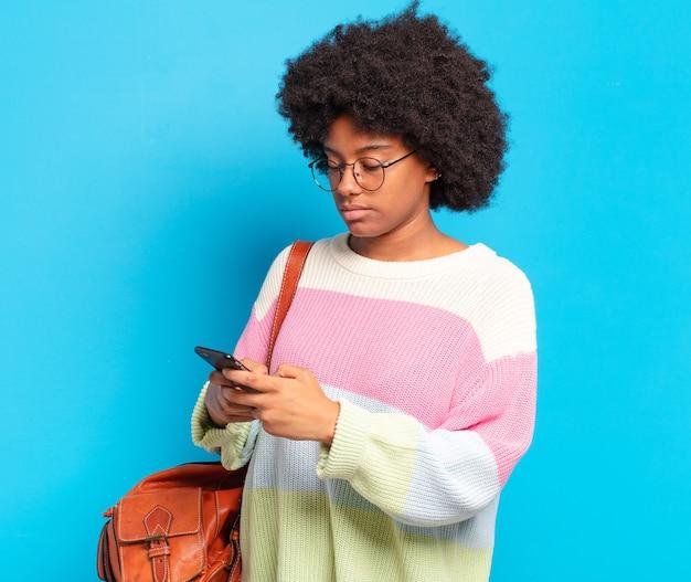 Jonge mooie afro student vrouw met een slimme telefoon