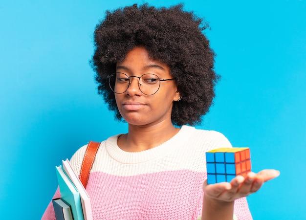 Jonge mooie afro-studentenvrouw die een intelligentieprobleem probeert op te lossen