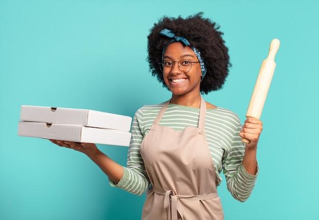 Jonge mooie afro vrouw chef-kok met een deegroller en pizza's