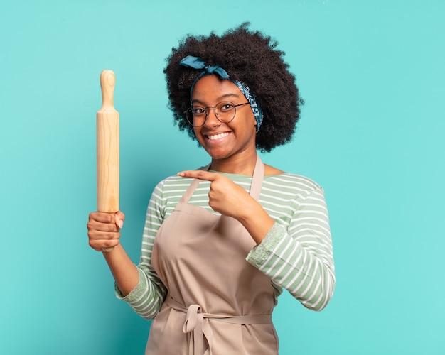 Jonge mooie afro vrouw chef-kok met een deegroller