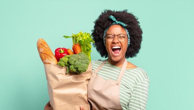 Jonge mooie afro-vrouw die agressief schreeuwt, erg boos, gefrustreerd, verontwaardigd of geïrriteerd kijkt, nee schreeuwt en een zak met groenten vasthoudt