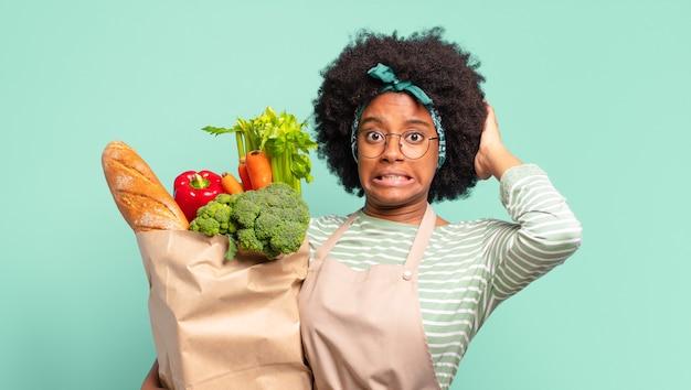 Jonge mooie afro-vrouw die er serieus, streng, ontevreden en boos uitziet, met open palm die een stopgebaar maakt en een zak met groenten vasthoudt
