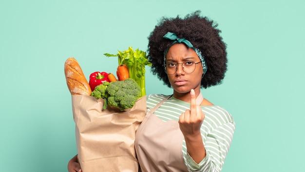Jonge mooie afro-vrouw die haar schouders ophaalt, zich verward en onzeker voelt, twijfelt met gekruiste armen en verbaasde blik en een zak met groenten vasthoudt