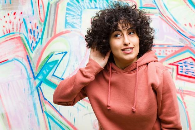 Jonge mooie afro vrouw die lacht, nieuwsgierig naar de zijkant kijkt, probeert te luisteren naar roddel of een geheime graffiti muur afluistert