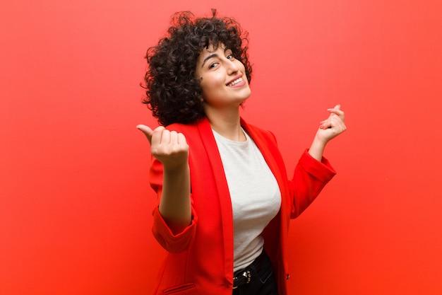 Jonge mooie afro vrouw die lacht, zich onbezorgd, ontspannen en gelukkig voelt, danst en naar muziek luistert, plezier maakt op een feestje