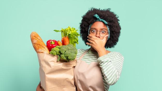 Jonge mooie afro-vrouw die mond bedekt met handen met een geschokte, verbaasde uitdrukking, een geheim bewaart of oeps zegt en een zak met groenten vasthoudt
