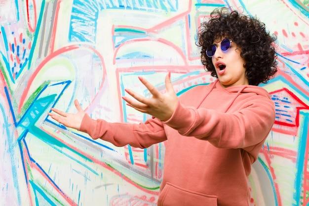 Jonge mooie afro-vrouw die opera uitvoert of bij een concert of show zingt, romantisch, artistiek en gepassioneerd tegen graffitimuur