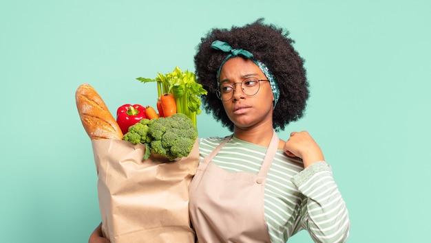 Jonge mooie afro-vrouw die trots en zelfverzekerd glimlacht en nummer één triomfantelijk laat poseren, zich een leider voelt en een zak met groenten vasthoudt