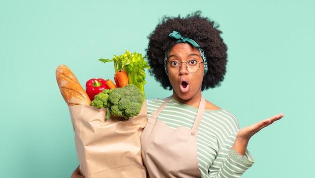 Jonge, mooie afro-vrouw die verbaasd en geschokt kijkt, met open mond naar beneden, een voorwerp vasthoudt met een open hand aan de zijkant en een zak met groenten vast