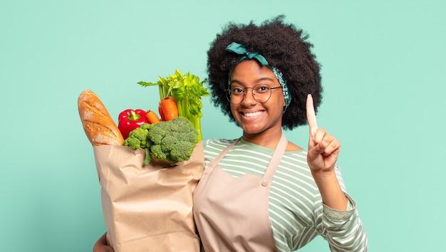 Jonge, mooie afro-vrouw die vrolijk en opgewekt lacht, hand zwaait, je verwelkomt en begroet, of gedag zegt en een zak met groenten vasthoudt