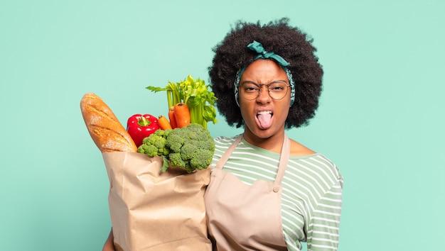 Jonge mooie afro-vrouw die walgt en geïrriteerd voelt, tong uitsteekt, niet van iets smerigs en vies houdt en een zak met groenten vasthoudt