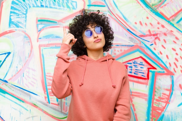 Jonge mooie afro-vrouw die zich als een geniale vinger trots in de lucht voelt na het realiseren van een geweldig idee, eureka tegen graffitimuur zeggen