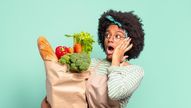 Jonge mooie afro-vrouw die zich blij, opgewonden en verrast voelt, naar de zijkant kijkt met beide handen op het gezicht en een zak met groenten vasthoudt