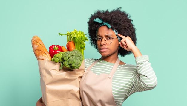 Jonge mooie afro-vrouw die zich boos, geïrriteerd, rebels en agressief voelt, de middelvinger omdraait, terugvecht en een groentetas vasthoudt