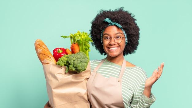 Jonge mooie afro-vrouw die zich gelukkig, verrast en opgewekt voelt, lacht met een positieve houding, een oplossing of idee realiseert en een zak met groenten vasthoudt