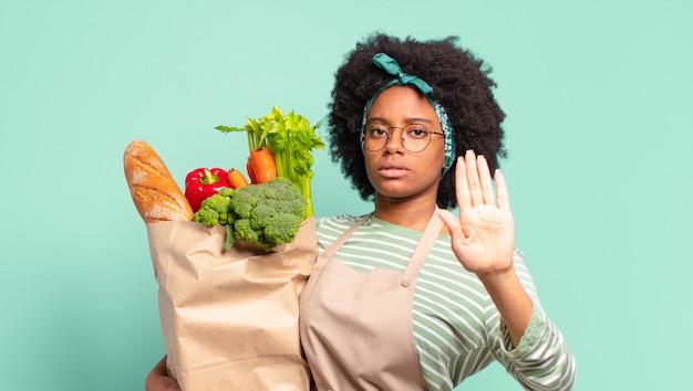 Jonge mooie afro-vrouw die zich trots, zorgeloos, zelfverzekerd en gelukkig voelt, positief lacht met duimen omhoog en een groentezak vasthoudt