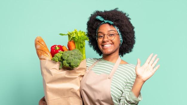 Jonge, mooie afro-vrouw die zich verward en verbaasd voelt, laat zien dat je gek, gek of gek bent en een zak met groenten vasthoudt
