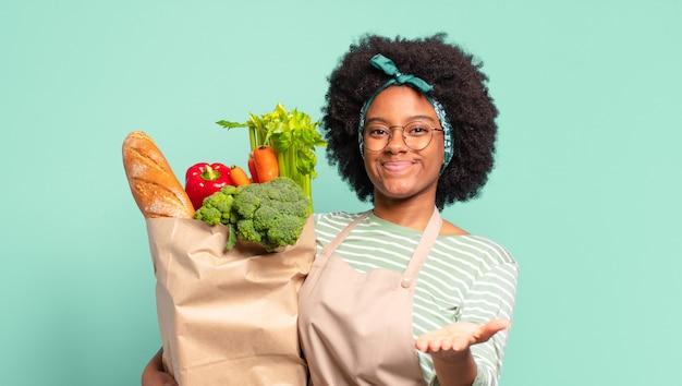 Jonge mooie afro-vrouw kijkt blij, verbaasd en verrast, lacht en realiseert zich geweldig en ongelooflijk goed nieuws en houdt een zak met groenten vast