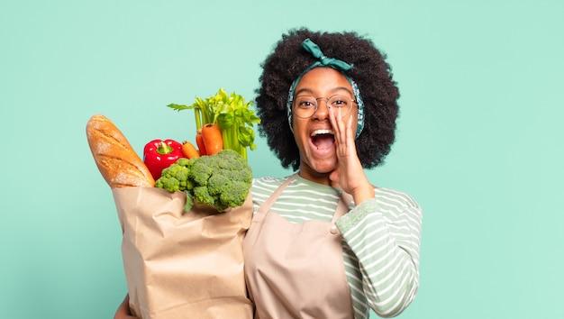 Jonge mooie afro-vrouw met vrolijke, zorgeloze, rebelse houding, grappen maken en tong uitsteken, plezier hebben en een zak met groenten vasthouden