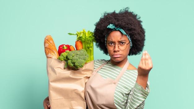 Jonge mooie afro-vrouw op profielweergave die ruimte vooruit wil kopiëren, denkt, zich voorstelt of dagdroomt en een groentenzak vasthoudt