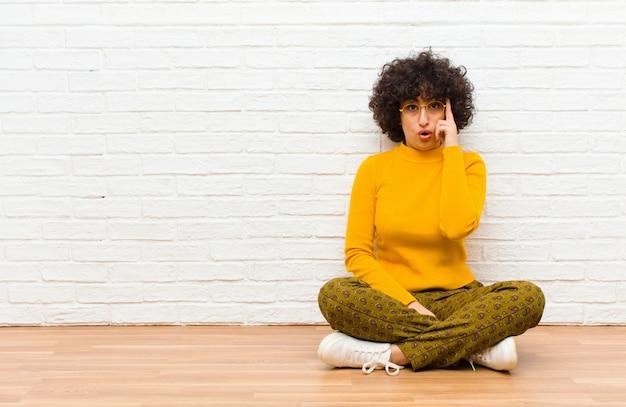 Jonge mooie afro vrouw op zoek verrast, met open mond, geschokt, het realiseren van een nieuwe gedachte, idee of concept zittend op de vloer