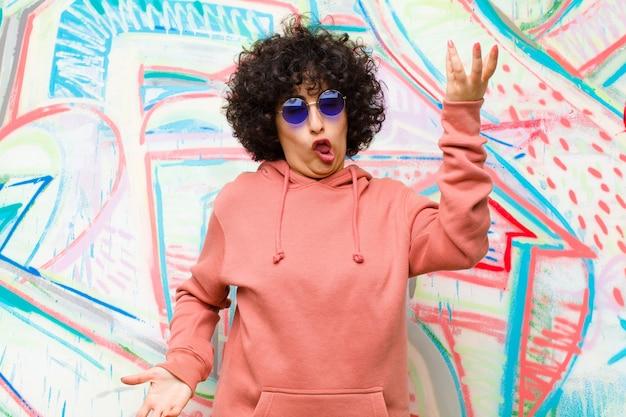 Jonge mooie afro-vrouw schouderophalend met een domme, gekke, verwarde, verbaasde uitdrukking, geïrriteerd en geen idee tegen graffiti