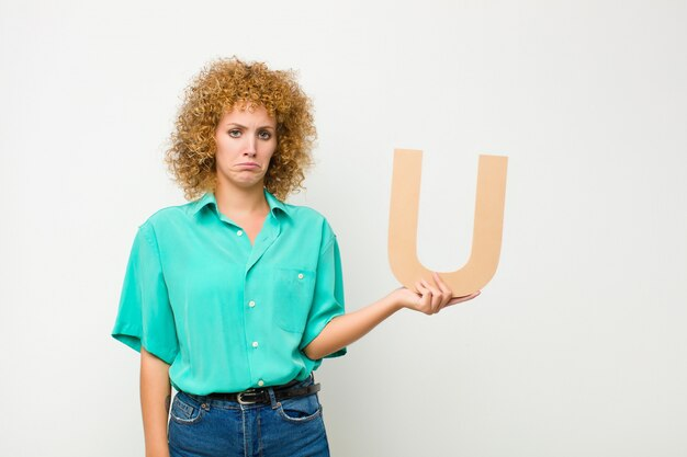 Jonge mooie afro vrouw verdrietig, depressief, ongelukkig, met de letter u van het alfabet om een woord of een zin te vormen.