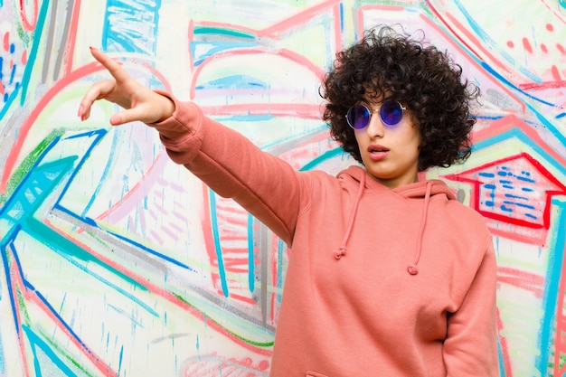 Jonge mooie afro-vrouw voelt zich geschokt en verrast, wijst en kijkt omhoog in ontzag met verbaasde blik met open mond tegen graffitimuur