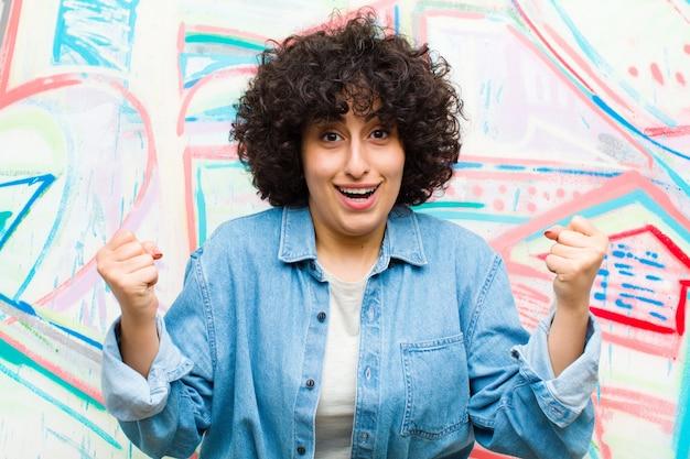 Jonge mooie afro-vrouw voelt zich geschokt, opgewonden en gelukkig, lacht en viert succes en zegt wow! tegen graffitimuur