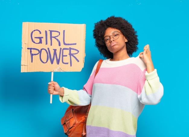 Jonge mooie afro vrouw vrouw met bordje met tekst: girl power