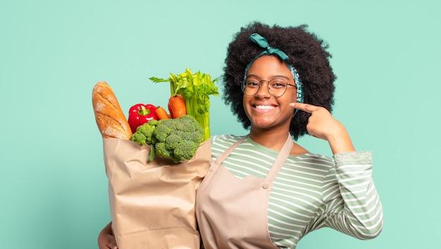 Jonge mooie afrovrouw die capice of geldgebaar maakt, die u zegt uw schulden te betalen! en met een zak met groenten
