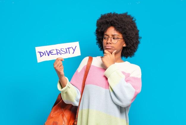 Jonge mooie afrovrouw die de banner van het diversiteitsconcept houdt
