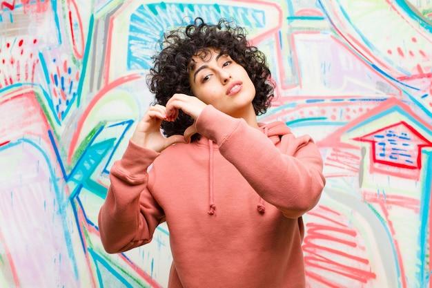 Jonge mooie afrovrouw die en gelukkig, leuk, romantisch en in liefde glimlacht voelt, die hartvorm met beide handen maakt tegen graffitimuur