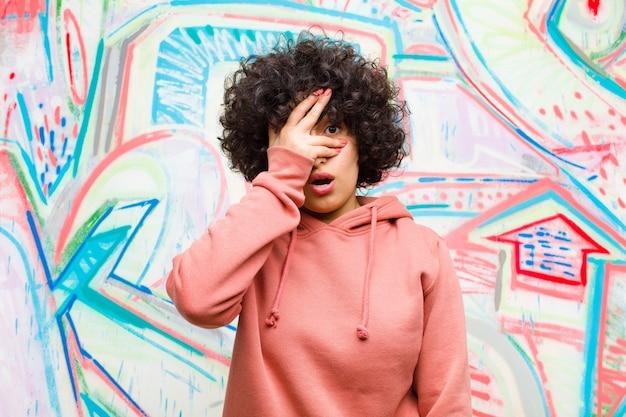 Jonge mooie afrovrouw die geschokt, bang of doodsbang kijkt, gezicht met hand behandelt en tussen vingers tegen graffiti gluren