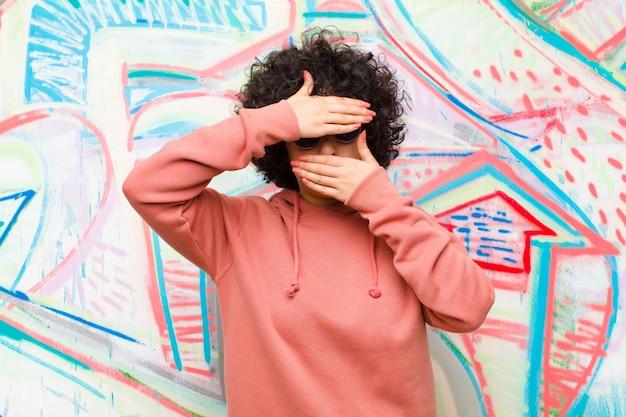 Jonge mooie afrovrouw die gezicht behandelt met beide handen die nee zeggen tegen de camera! afbeeldingen weigeren of foto's verbieden tegen een graffitimuur
