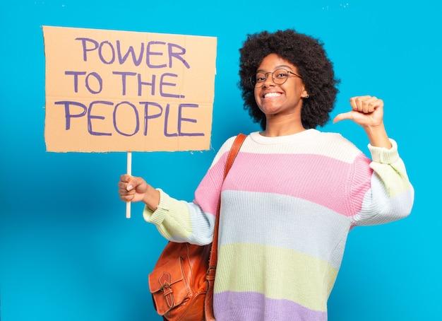 Jonge mooie afrovrouw die met een macht aan de mensen protesteert