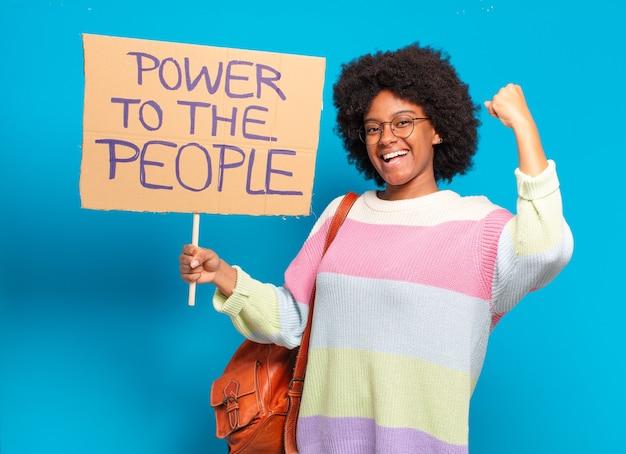 Jonge mooie afrovrouw die met een macht aan de mensenbanner protesteert