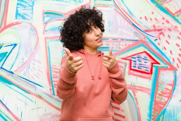 Jonge mooie afrovrouw die met het positieve, succesvolle, gelukkige houding glimlachen glimlachen, die kanon maken ondertekenen met handen tegen graffitimuur