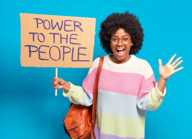 Jonge mooie afrovrouw die protesteert met een macht aan de mensenbanner