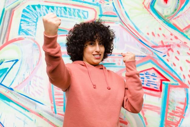 Jonge mooie afrovrouw die triomfantelijk schreeuwt, kijkend als opgewonden, gelukkige en verraste winnaar, vierend tegen graffitimuur