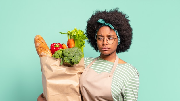 Jonge mooie afrovrouw die vrolijk glimlacht, zich gelukkig voelt en een concept in exemplaarruimte met palm van hand toont en een groentenzak vasthoudt