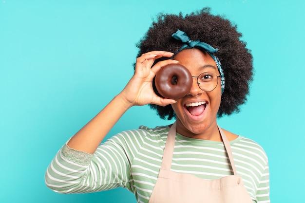 Jonge mooie afrovrouw met een donut