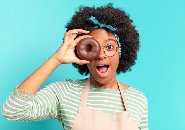 Jonge mooie afrovrouw met een doughnut