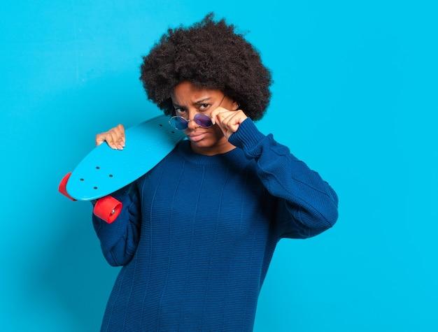 Jonge mooie afrovrouw met een skatebord