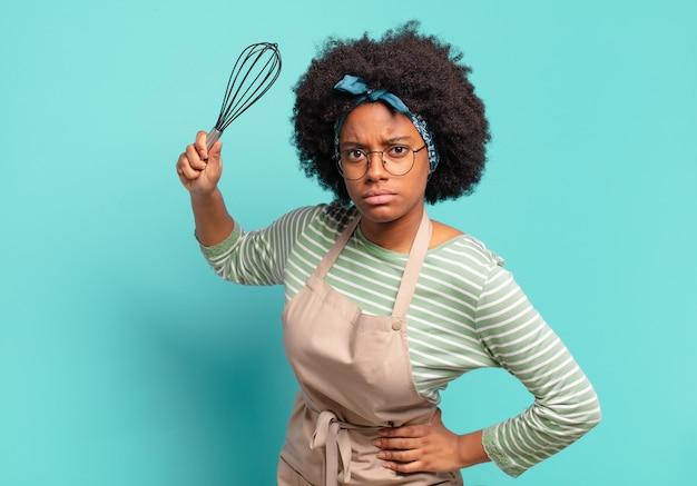 Jonge mooie afrovrouwenchef-kok met een mixer