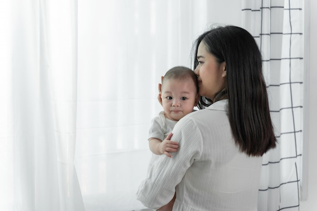 Jonge mooie aisan-moeder met haar kleine schattige pasgeboren baby